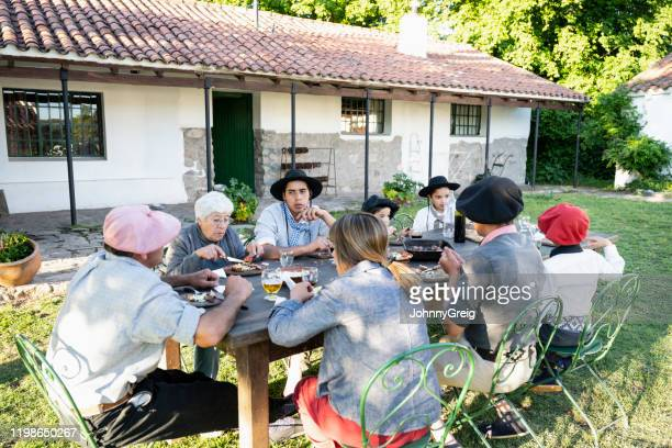 Three-generation Argentine gaucho family dining outdoors