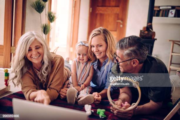 Three-generation family with little baby girl watching cartoons on laptop