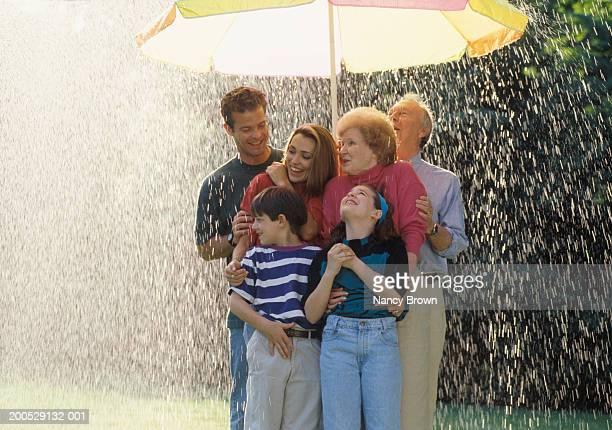 Three-generational family standing under sun umbrella in rain, smiling