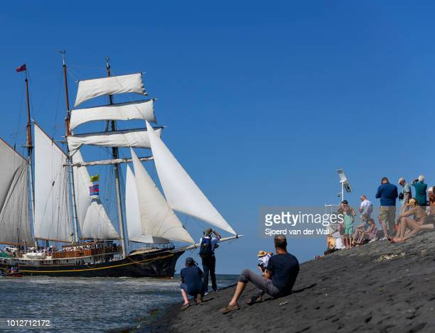 Threemasted topsail schooner Gulden Leeuw entering the port of Harlingen during the finish of the 2018 Tall Ship Race with people on shore watching...