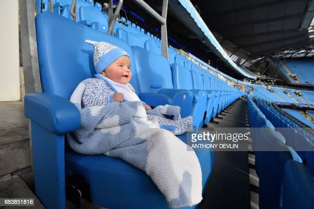 Threemonth old Blake Trevalyan sits on a seat ahead of kick off of the English Premier League football match between Manchester City and West...