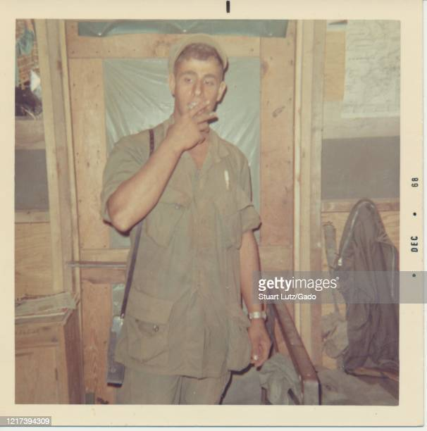 Three-quarter length frontal shot of a young, uniformed serviceman, standing in front of a wooden doorway in a small barrack and looking off to one...