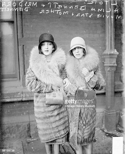 """Three-quarter length portrait of actress Alma Bennett, star of the 1927 film """"Long Pants,"""" standing with her mother in front of a building in..."""
