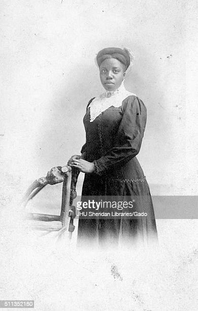 Threequarter length portrait of African American woman wearing dark dress with serious facial expression hands rested on wooden chair 1915