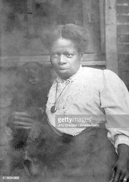 Three-quarter length portrait of an African American Woman in front of a brick wall and window, wearing a white blouse and a dark dress, wearing a...