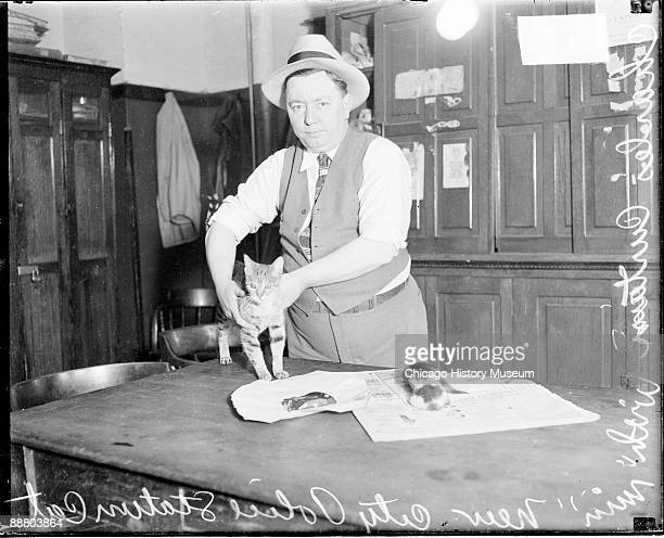 Threequarter length portrait of Charles Curtain of the Chicago Police Department standing at a table with Min a cat in a room in the New City police...