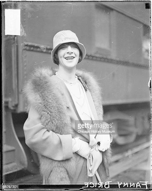 Threequarter length portrait of Fanny Brice looking toward the camera standing in front of a passenger train car in a railroad station in Chicago...