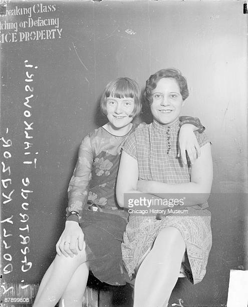 Threequarter length portrait of Gertrude Tialkowski and Dolly Kazor sitting in front of a dark wall in a room in a police station in Chicago Illinois...