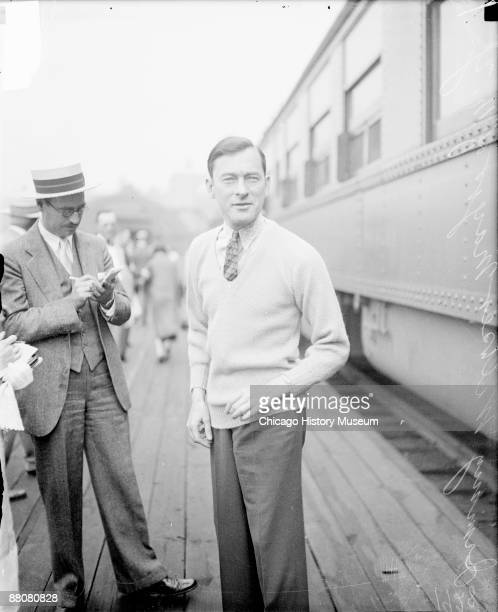 Threequarter length portrait of Jimmy Walker Mayor of New York City looking toward the camera standing next to a passenger train car in a railroad...