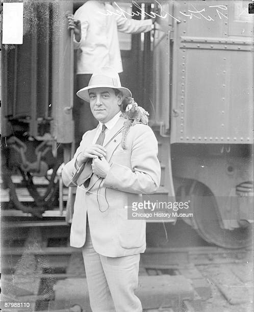 Threequarter length portrait of Tito Schipa tenor and composer standing in front of train tracks in a railroad station in Chicago Illinois 1928 Two...