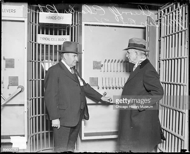 Threequarter length portrait of Warden Ed Fogarty and Deputy Sheriff Charles Peters of the Chicago Police Department standing in front of a control...