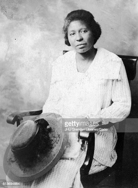 Three-quarter length seated portrait of African American woman with a neutral expression in front of a painted backdrop, with a hat on her lap and...