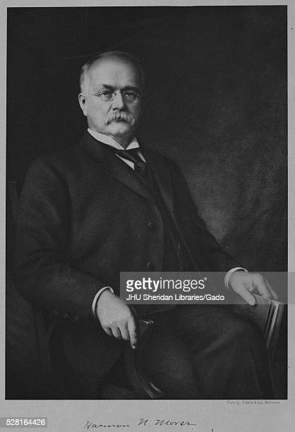 Threequarter length seated portrait of American chemist Harmon Northrop Morse with a neutral expression holding a book in his left hand 1900