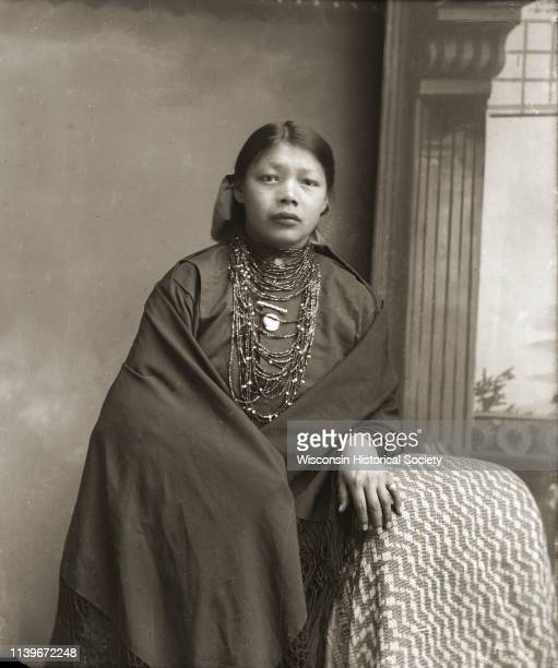 Three-quarter length studio portrait of a Ho-Chunk woman posing standing in front of a painted backdrop with her left hand on a draped chair, Black...
