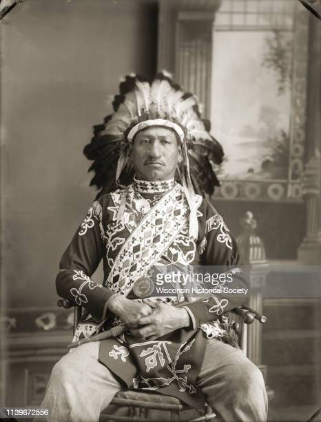 Threequarter length studio portrait of Thomas Thunder Black River Falls Wisconsin 1910 He is wearing elaborate HoChunk regalia including eagle...