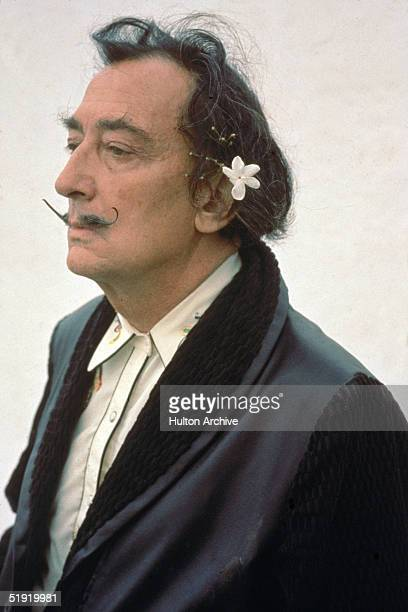Three-quarter profile portrait of Spanish surrealist painter Salvador Dali dressed in a smoking jacket with a flower in his hair, early 1980s.