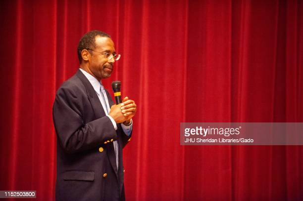 Three-quarter profile view of neurosurgeon Ben Carson holding a microphone during an a Milton S Eisenhower Symposium at the Johns Hopkins University,...