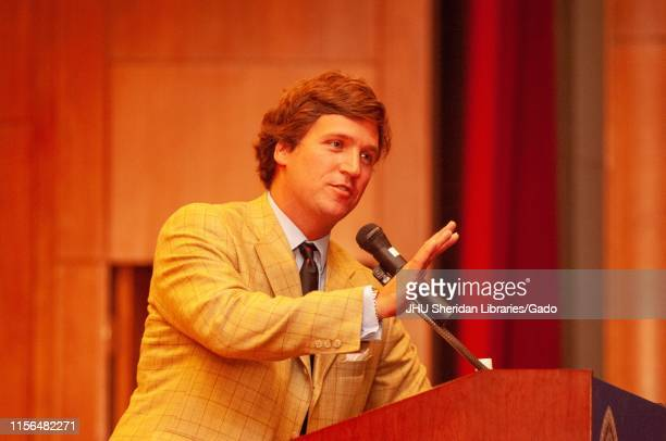 Three-quarter profile view of political commentator Tucker Carlson, speaking from a podium during a Milton S Eisenhower Symposium at the Johns...