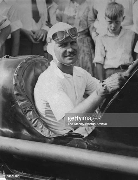 Three-time Indianapolis 500 winner, Wilbur Shaw poses for a portrait from inside his race car, circa 1937.