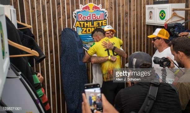 Three-time WSL World Champion Gabriel Medina, of Brazil, hugs fellow countryman Filipe Toledo, facing camera, in the locker room after Medina beat...