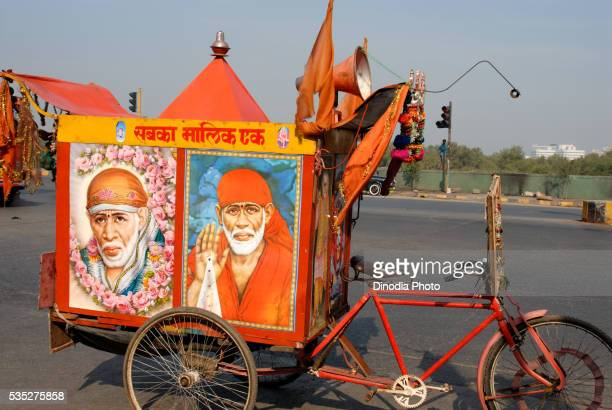 Three-wheeled bicycle pulling a cart featuring portrait of Sai Baba with a loudspeaker in Mumbai, Maharashtra, India.