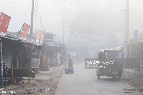 COX'S BAZAR BANGLADESH DECEMBER 20 A threewheeler passes through a market area on a foggy morning in Cox's Bazar Bangladesh on December 20 2017...