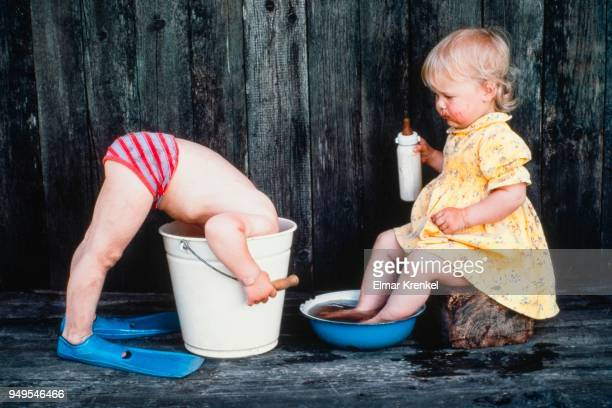 Three-year old girl bathes her feet, boy puts head in bucket, Austria