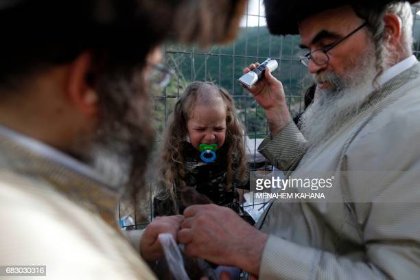 Threeyear old Jewish children take part in the traditional Halake ceremony a first hair cut from his ultraorthodox father during a celebration at the...