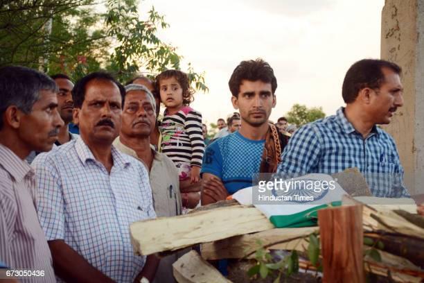 Threeyearold daughter Alina with martyr CRPF jawan Surender Kumar's body at native village Ner Chowk on April 25 2017 in Mandi India