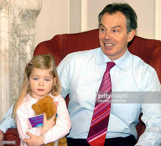 Threeyearold Elenor Williams from Warrington sits on the lap of Britain's Prime Minister Tony Blair during his meeting with her mother Christine and...