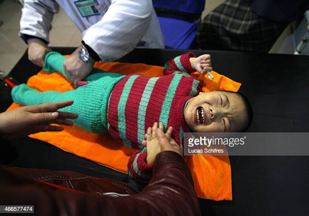 Threeyearold Gao Xiang cries from pain under the massage aimed to help her stiff legs damaged since birth while her mother holds her hand in Cerebral...