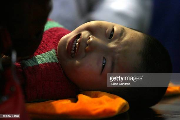 Threeyearold Gao Xiang cries from pain under the massage aimed to help stiff legs damaged since birth in Cerebral Palsy Hospital on November 15 2007...