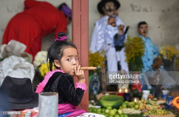 Three-year-old girl smokes a cigar during the Saint Simon celebrations in San Andres Itzapa, Guatemala, on October 28, 2019. - Thousands believe that...
