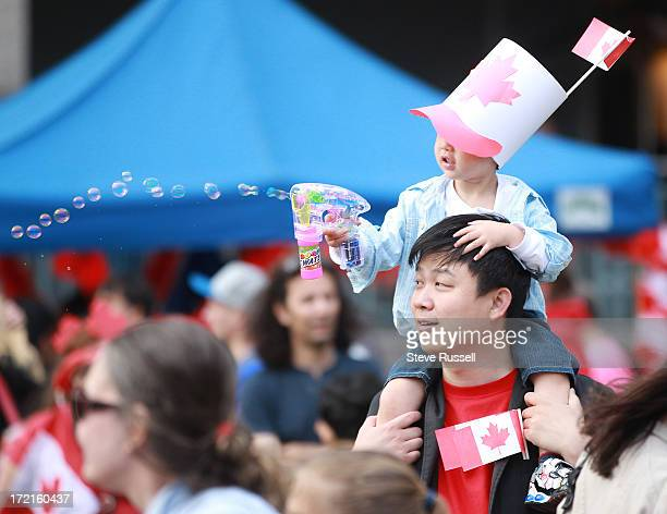 Threeyearold Howard fires off some bubbles from on top of his father Jason Lin's shoulders during Canada Day celebrations at Mel Lastman Square