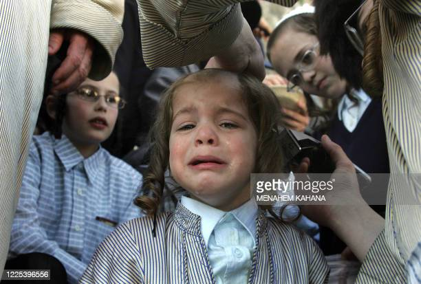 Three-year-old Jewish boy cries as he is having his first hair cut near the grave of Rabbi Shimon Bar Yochai and during the holy day of Lag BaOmer,...