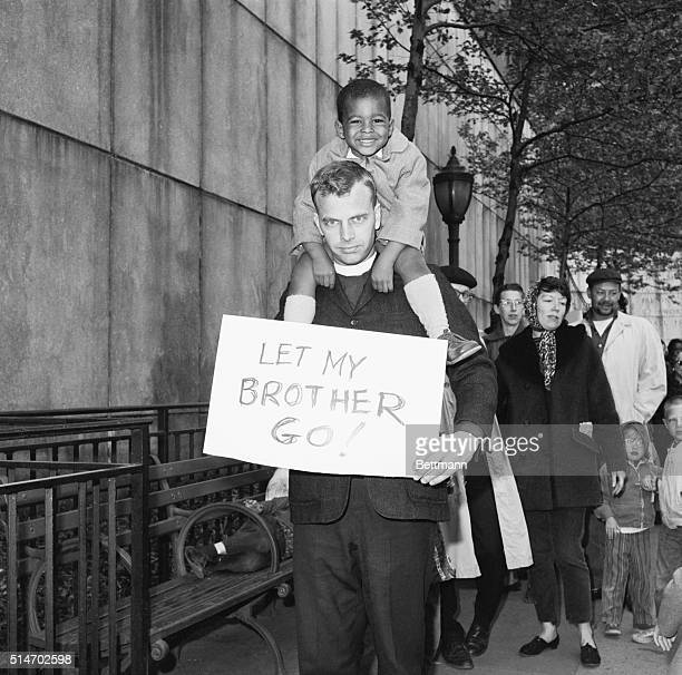 Threeyearold Jonathan Flemister rides on the shoulders of Reverend Lincoln Dring during a antisegregation protest held at the United Nations Building...