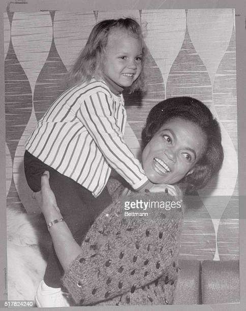 Threeyearold Kitt McDonald smiles prettily for cameramen as she gets a lift from mommy singeractressdancer Eartha Kitt during a press conference here...