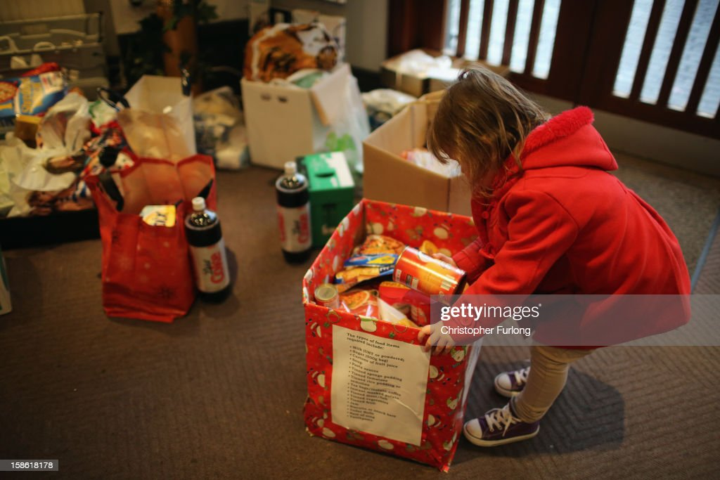 Three-year-old Lexie Hay looks through donations of food at Liverpool Foodbank as she waits with her mum to collect essential provisions for Christmas on December 21, 2012 in Liverpool, England. With Christmas only days away, volunteers at the Central Liverpool Foodbank at the Frontline Trust, have seen one of their busiest days of the year as they give out free food for the needy. The centre has been giving out festive treats as well as its normal food donation, feeding over 1000 individuals in its first year, including over 300 children.