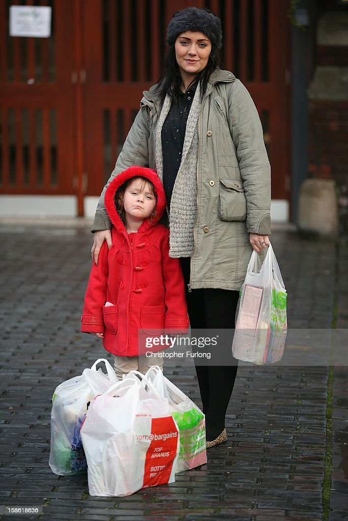 Three-year-old Lexie Hay stands with her mum Samantha Winter pose outside Liverpool Foodbank after collecting essential provisions for Christmas on December 21, 2012 in Liverpool, England. With Christmas only days away, volunteers at the Central Liverpool Foodbank at the Frontline Trust, have seen one of their busiest days of the year as they give out free food for the needy. The centre has been giving out festive treats as well as its normal food donation - feeding over 1000 individuals in its first year, including over 300 children.