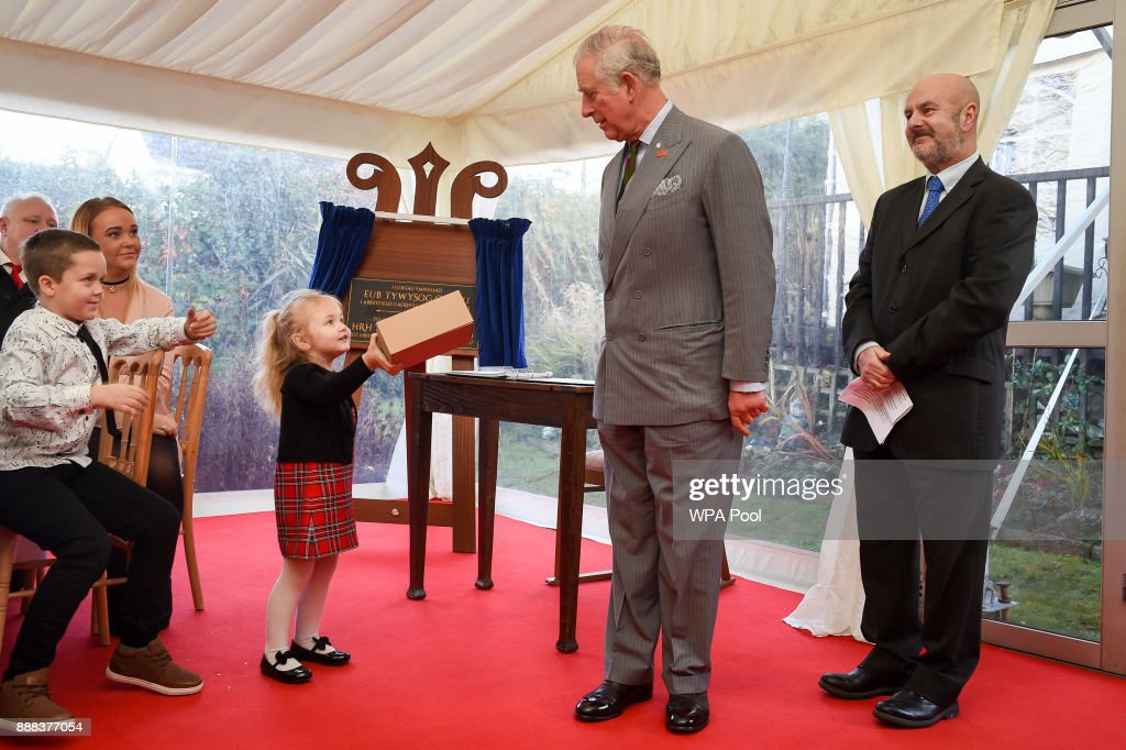 Three-year-old Lexi-Mai, presents the Prince Charles, Prince of Wales a box of handmade cards, made by residents of the Abbeyfield supported housing service in Caerphilly, during his visit to the centre on December 8, 2017 in Caerphilly, Wales.
