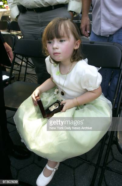 Three-year-old Patricia Smith looks at the shield that belonged to her mother, Police Officer Moira Smith, the only woman among 23 NYPD cops killed...
