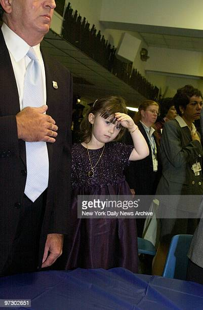Three-year-old Patricia Smith salutes as a plaque in memory of her mother, Police Officer Moira Smith, is unveiled in the basement of Epiphany Church...