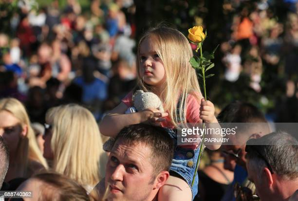 Threeyearold Ruby Tindall watches from her father Lee's shoulders during a vigil to commemorate the victims of the May 22 attack on Manchester Arena...
