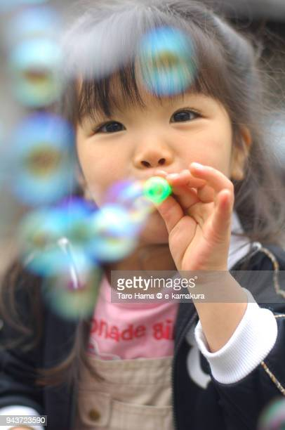 A three-years-old girl blowing bubbles on the street