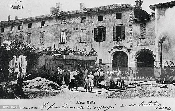 Threshing of wheat with a steam engine in front of Casa Natta in Pombia ca 1905 postcard Piedmont Italy 20th century