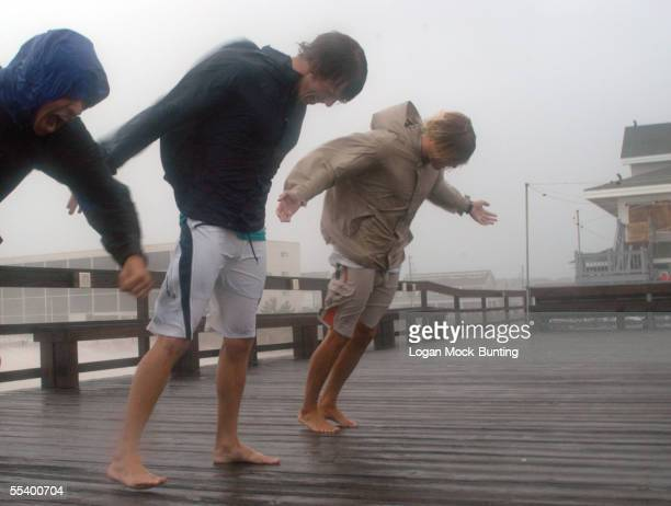 Thrill seekers lean into the wind while standing on the Oceanic pier in the heavy rains and high winds brought on by Hurricane Ophelia as it closes...