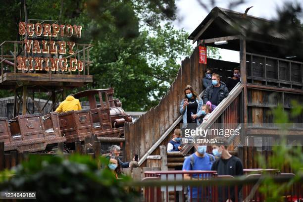 Thrill seekers wear face masks as they queue for a ride at Chessington World of Adventures Resort in chessington Greater London on July 4 on the...