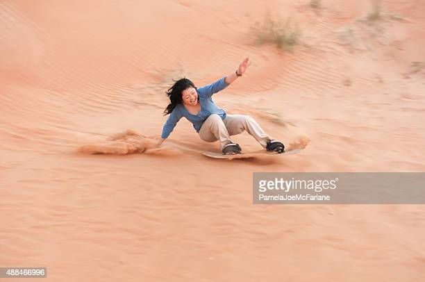 Thrill Seeking Woman Adventure Tourist Sandboarding in Sharjah, Dubai Desert
