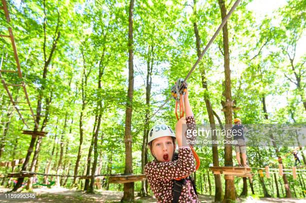 thrilled girl on zip line in adventure park - flying fox stock pictures, royalty-free photos & images