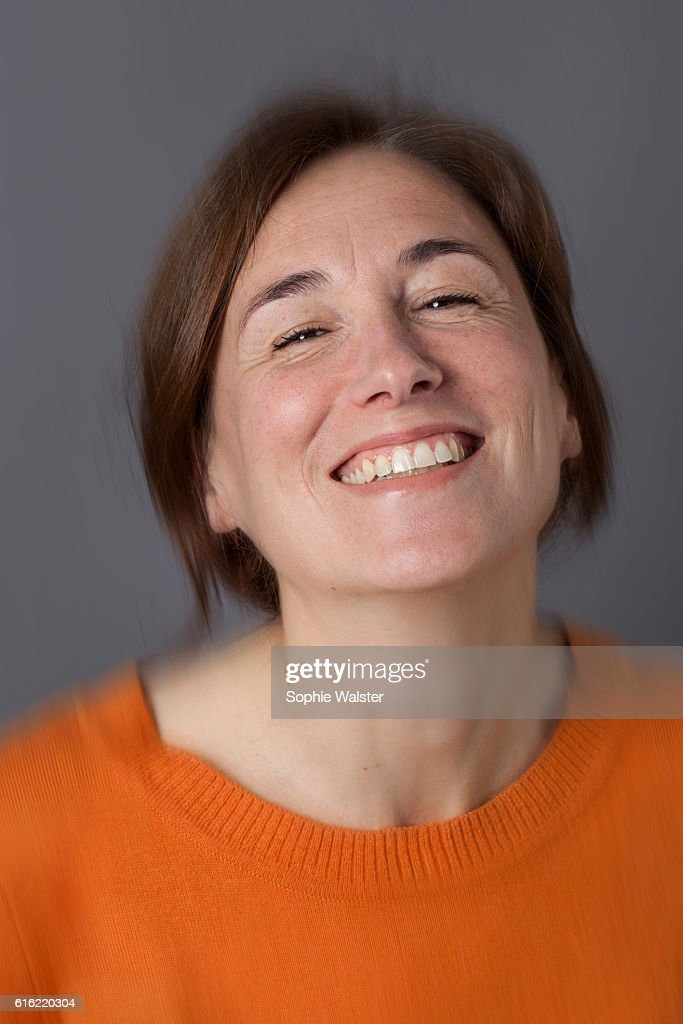 thrilled middle aged woman with brown hair laughing, blur effects : Stockfoto